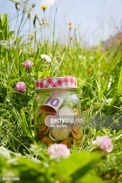 Euro bank note and coins in jar