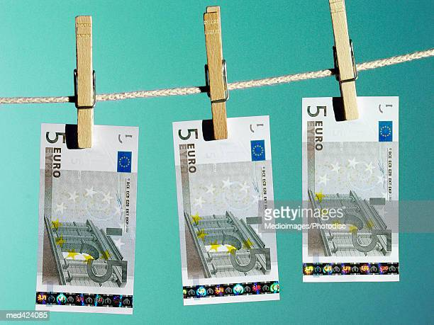euro bank notes hung on a clothes line with clothes pegs - five euro banknote stock photos and pictures