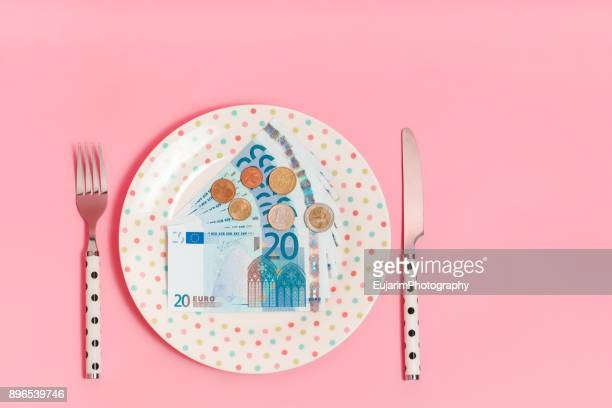 Euro banknotes and coins on a polka dots pattern plate