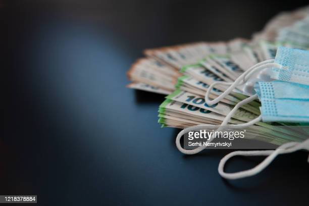 euro banknotes and pills, on black background, concept of treatment costs, paid medicine, mask for respiratory protection. virus protection. health care reform. copy space, place for text - currency stock pictures, royalty-free photos & images