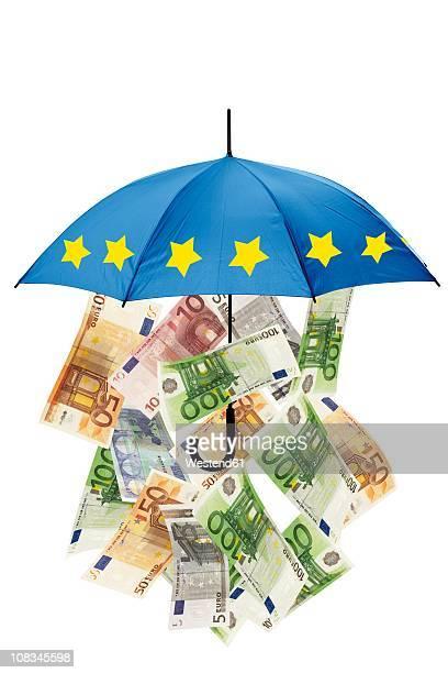 euro banknotes under umbrella against white background - banconote euro foto e immagini stock