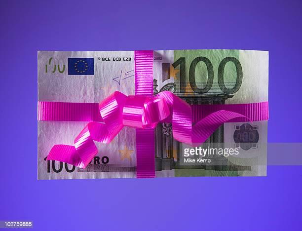 100 euro bill tied with a pink bow - altruismo foto e immagini stock