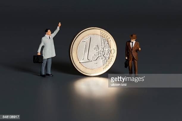 1 Euro coin and businessmen