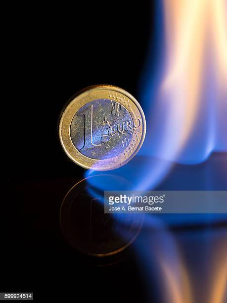 Euro coin burned by the fire of the crisis