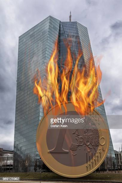 Euro coin going up in flames in front of the European Central Bank building, ECB