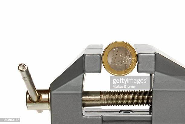 Euro coin held in a vice