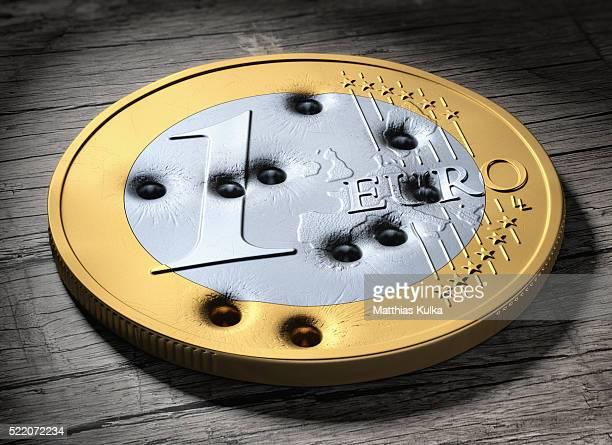 Euro coin with bullet holes