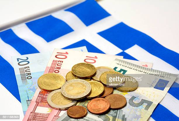 Euro coins and notes on a flag of Greece