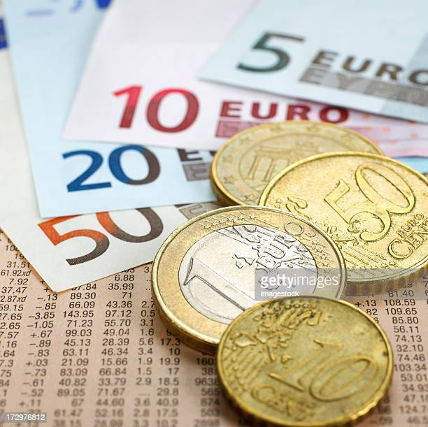 Euro coins and notes on financial newspaper
