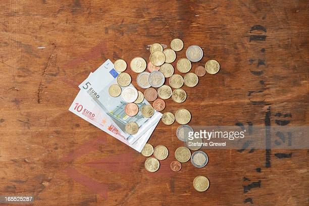 euro coins and notes on table - five euro banknote stock photos and pictures