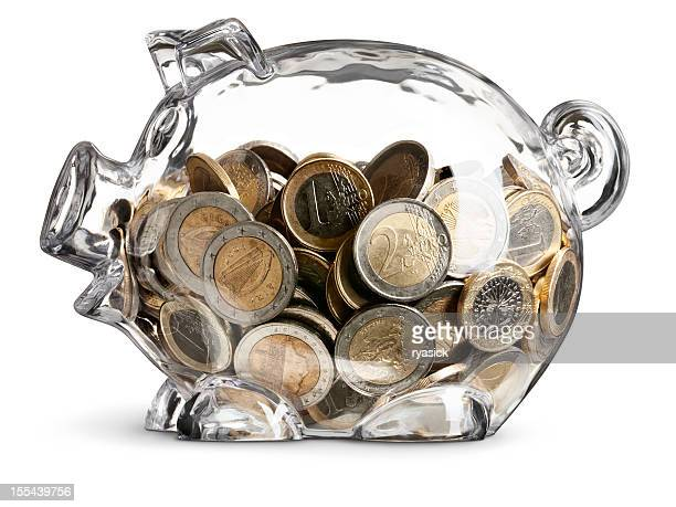 euro coins in nearly full clear savings piggy bank - piggy bank stock photos and pictures