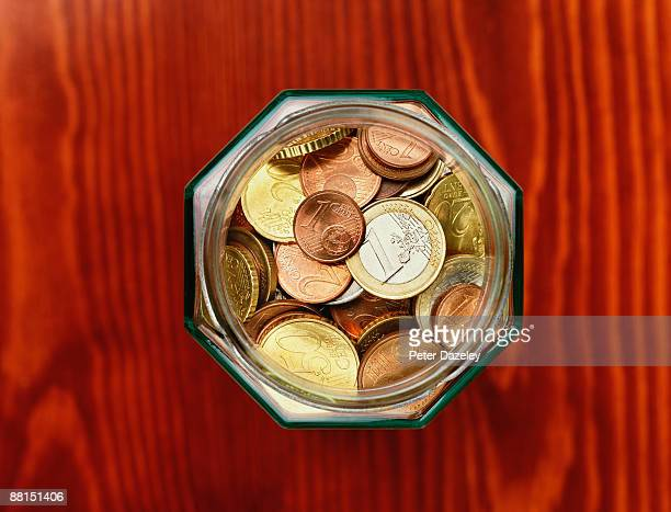 Euro coins in savings jar on wood background.