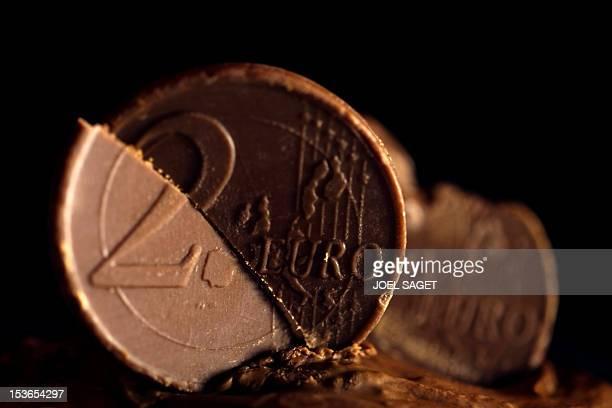 2 euro coins made of chocolate is split on December 7 2011 in Paris AFP PHOTO JOEL SAGET
