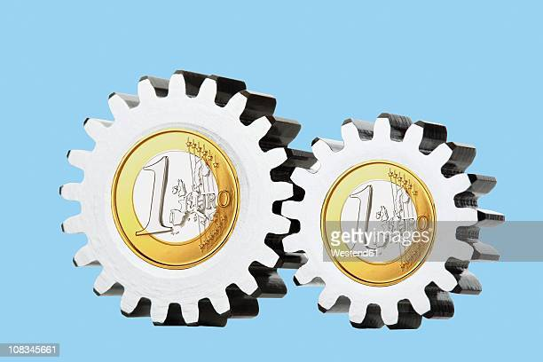 1 euro coins with cogwheels, close up - monetary policy stock pictures, royalty-free photos & images