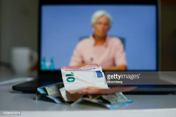 Euro currency banknotes sit in front of a laptop displaying Christine Lagarde president of the European Central Bank during a live stream video of...