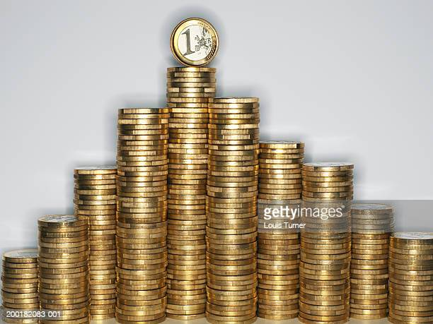 Euro Currency:  One Euro coin balanced on stacked Euro coins, close-up