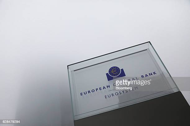 A euro currency symbol sits on a sign as the European Central Bank skyscraper headquarter offices stand shrouded in fog beyond ahead of a news...