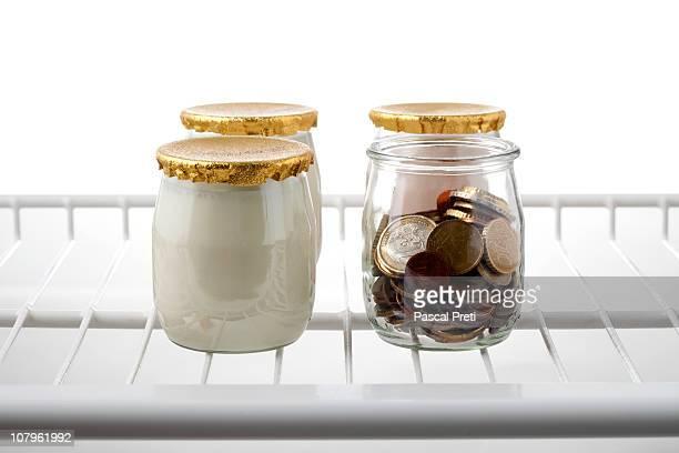 Euro money in a fridge with yogurts