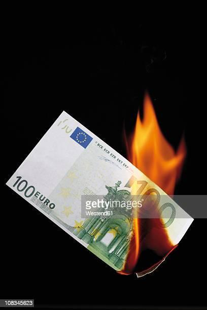 100 euro note burning against black background