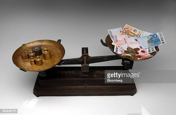 Euro notes and coins are balanced on a scale in Paris France on Monday April 27 2009 German Finance Minister Peer Steinbrueck said that the euro...