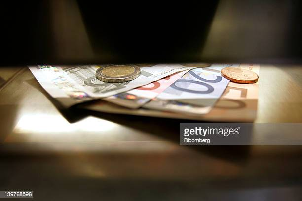 Euro notes and coins are seen in this arranged photograph at a currency exchange in Helsinki Finland on Friday Feb 24 2012 Finland's government...