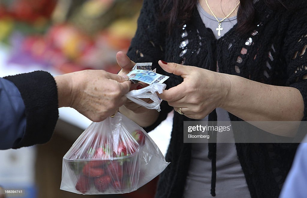 Euro notes are exchanged for payment for a bag of fresh strawberries at an open market in Ljubljana, Slovenia, on Wednesday, May 8, 2013. Slovenia's recession will stretch into next year on weak domestic demand as the euro-area country teeters on the brink of needing an international bailout, the European Commission said. Photographer: Chris Ratcliffe/Bloomberg via Getty Images