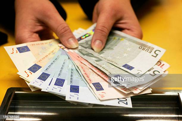 Euro notes are seen at a currency exchange in this arranged photograph in Helsinki Finland on Friday Feb 24 2012 Finland's government decided to send...