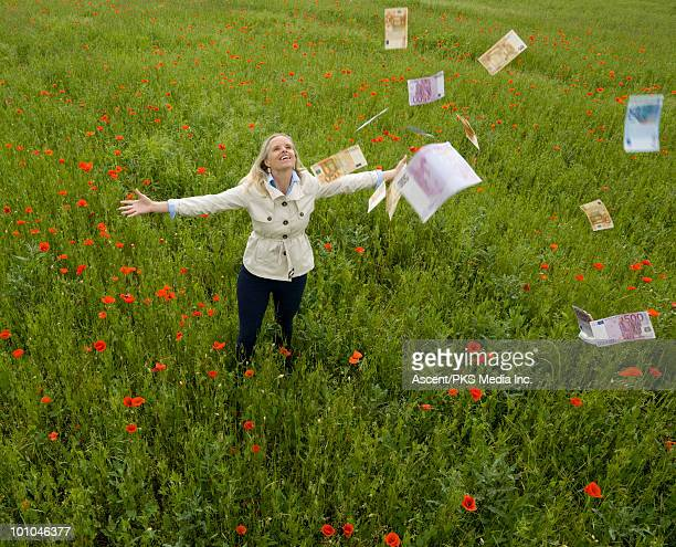 Euro notes fall through the air to woman in field