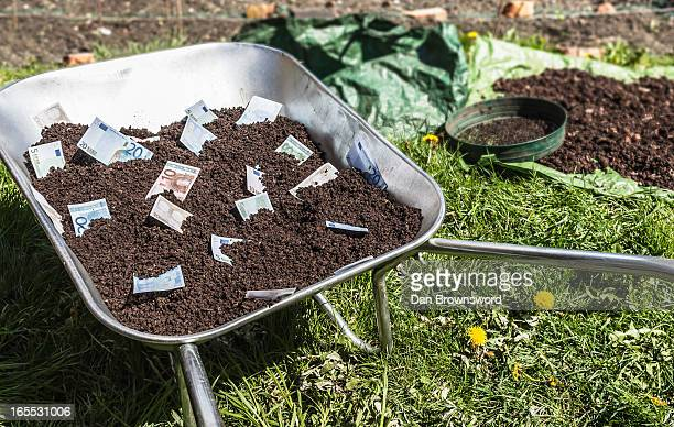 Euro notes in wheelbarrow of dirt