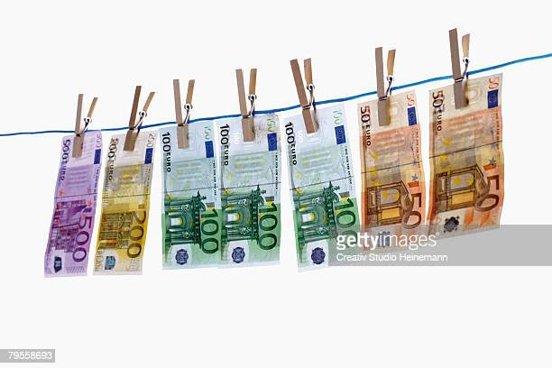 euro notes on clothesline - money laundering stock photos and pictures