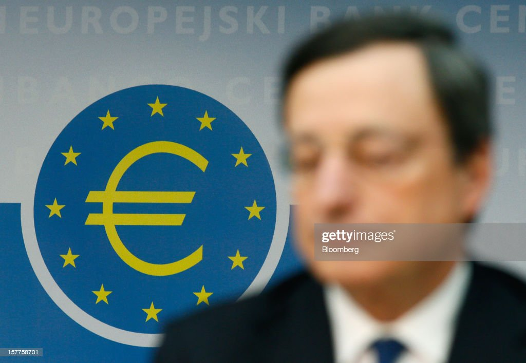 A euro sign is seen on a wall behind Mario Draghi, president of the European Central Bank (ECB), during a news conference at the bank's headquarters in Frankfurt, Germany, on Thursday, Dec. 6, 2012. The European Central Bank cut its economic and inflation forecasts and Draghi said weakness will persist into next year, leaving the door ajar for further interest-rate cuts. Photographer: Ralph Orlowski/Bloomberg via Getty Images