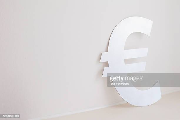 Euro symbol against wall