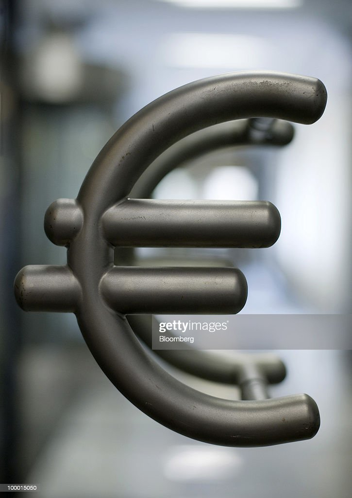 Euro symbol door handles hang from a glass door inside Poland's central bank building (NBP), in Warsaw, Poland, on Thursday, May 20, 2010. The zloty extended its decline as Polish officials indicated they are comfortable with its depreciation and the benchmark stock index dropped to a two-month low on growing concern Europe's debt crisis will deepen. Photographer: John Guillemin /Bloomberg via Getty Images