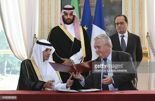 Eurocopter senior vice president for sales and customer relations Olivier Lambert exchanges documents with Saudi Foreign Minister Adel alJubeir after...