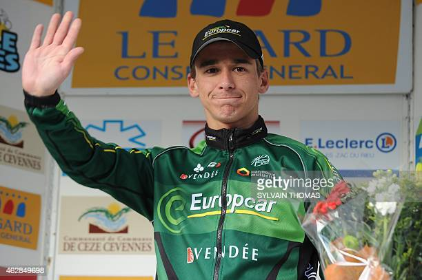 Europcar's team French cyclist Bryan Coquard waves as he celebrates on the podium after winning the third stage of the 45th Etoile de Besseges...