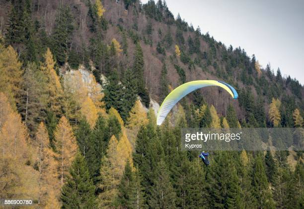 Europe, Austria, Salzburg Area, Tennengau, 2017: View Of Austrian Alps With Woodland Or Forest Paraglider Using Paragliding Equipment To Fly