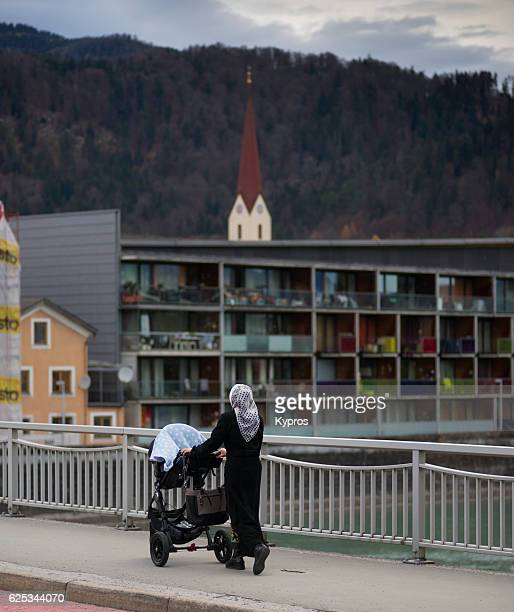 Europe, Austria, Tyrol, Kufstein, View Of Woman Wearing Headscarf Walking Pushing Pram. Many Refugees In This Area Muslim Woman Walking, Many Refugees In This Area