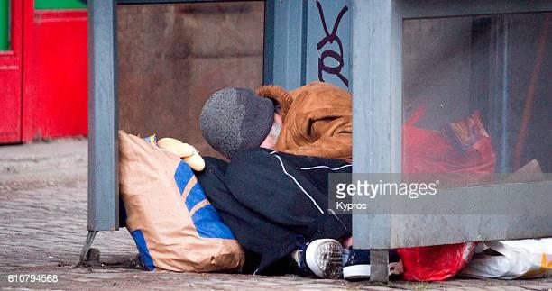 Europe, Czech Republic, Prague, View Of Homeless Man Sleeping Inside Telephone Booth