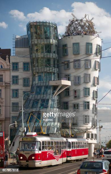 europe, czech republic, prague, view of the dancing house office building with red tram - republic steel company stock pictures, royalty-free photos & images