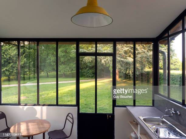 europe, france, bourgogne, epoisses, kitchen with large glass window overlooking the garden - erker stockfoto's en -beelden