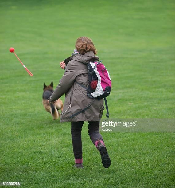 Europe, Germany, Bavaria, Munich, View Of Woman Walking Alsatian (German Shepherd) Dog In Park
