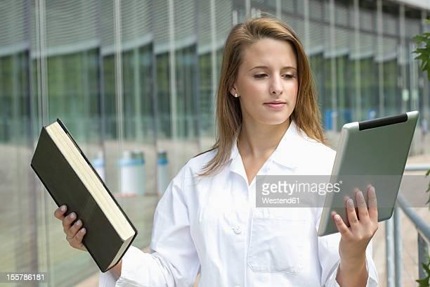 Europe, Germany, North Rhine Westphalia, Duesseldorf, Medical student comparing book with digital tablet