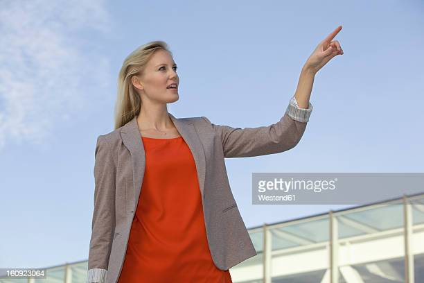 Europe, Germany, North Rhine Westphalia, Duesseldorf, Young woman pointing finger in air