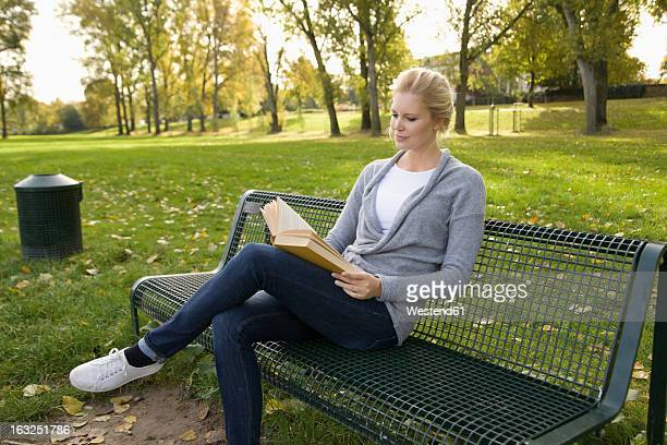 Europe, Germany, North Rhine Westphalia, Duesseldorf, Young woman reading book on park bench