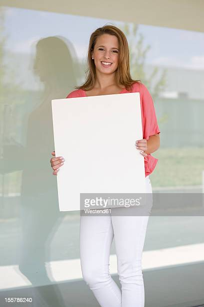 Europe, Germany, North Rhine Westphalia, Duesseldorf, Young woman with placard, smiling, portrait