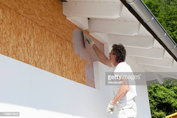 Europe, Germany, Rhineland Palatinate, Man insulating polystyrene