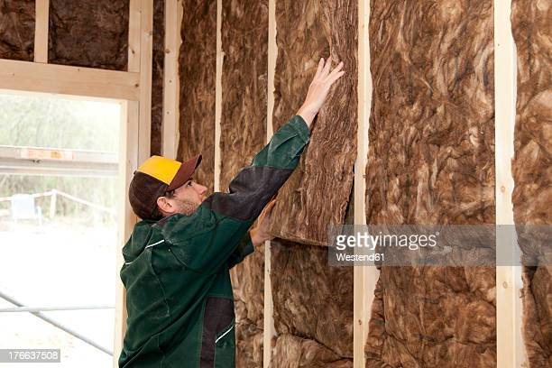 Europe, Germany, Rhineland Palatinate, Worker placing thermal felt insulation inside house