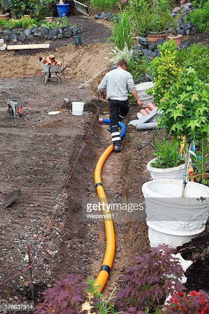 Europe, Germany, Rhineland Palatinate, Worker transferring drainage pipe