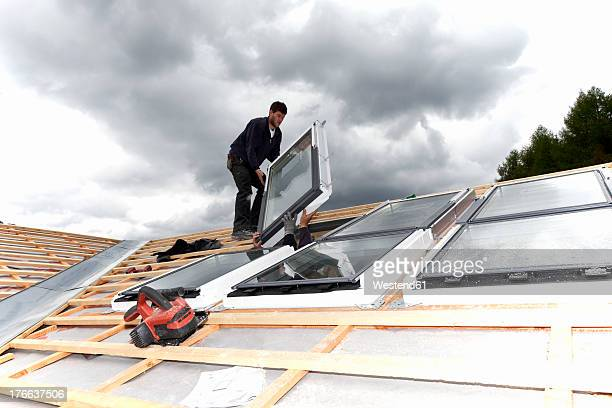 europe, germany, rhineland palatinate, workers installing roof windows - installieren stock-fotos und bilder