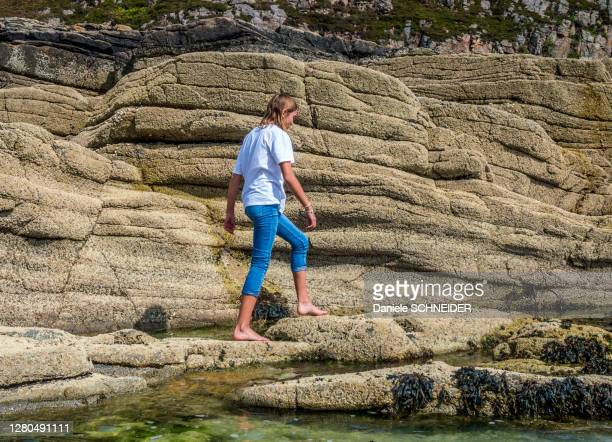 europe, great britain, scotland, hebrides, south-east of the isle of skye, young tourist walking on the rocks by the sea at point of sleat - hebriden inselgruppe stock-fotos und bilder